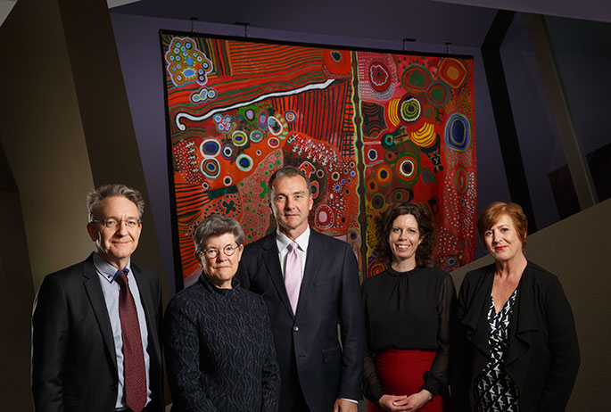 Group portrait of men and women standing in front of a painting