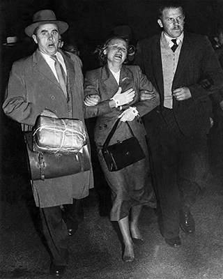 Photo taken at night showing distressed woman flanked by two men in suits holding her arms