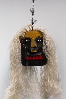 Cultural mask with brown, yellow ochre and red facial tones, and white wavy hair.