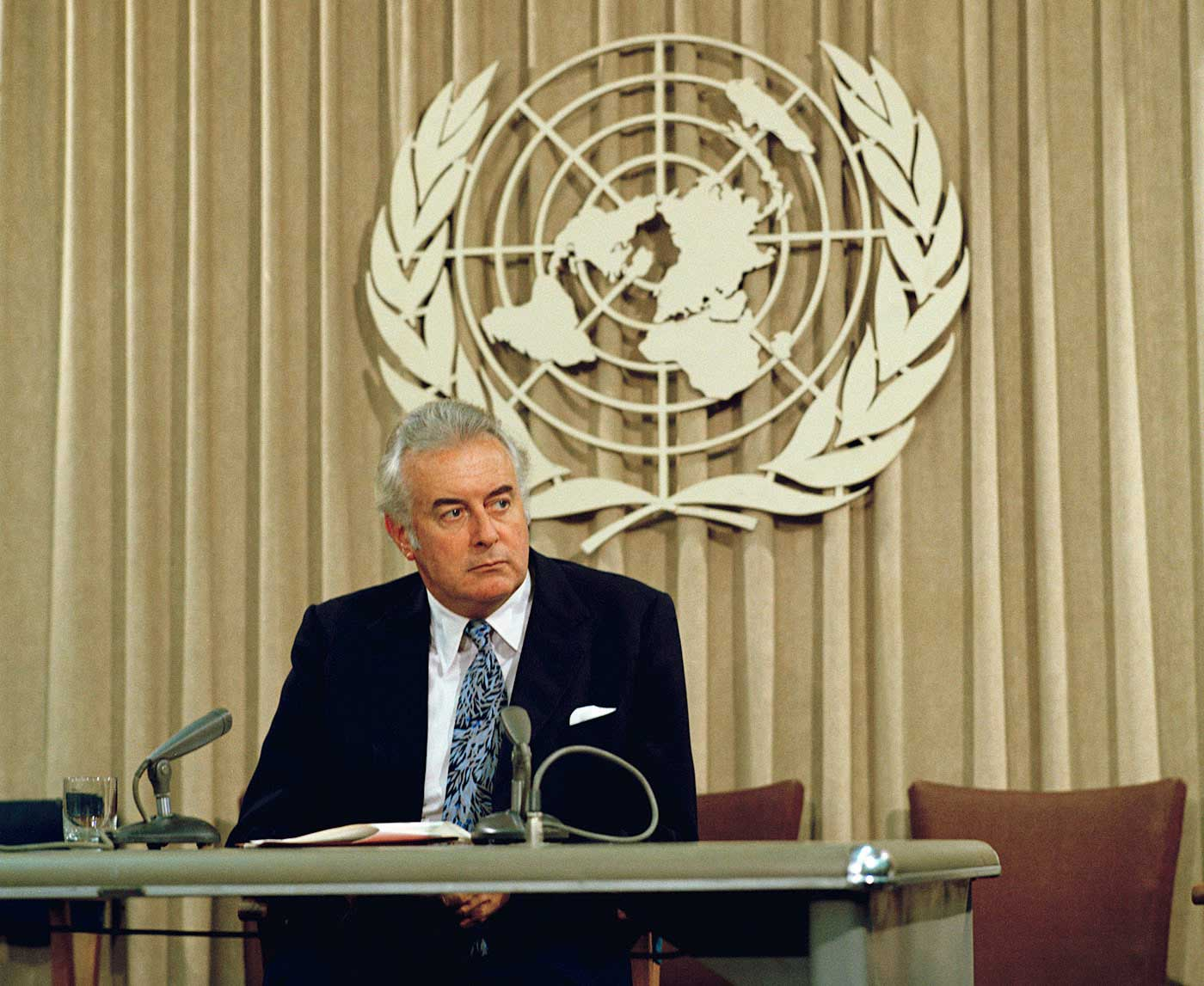 Colour photo of middle-aged man in suit sitting behind desk with UN symbol in background.