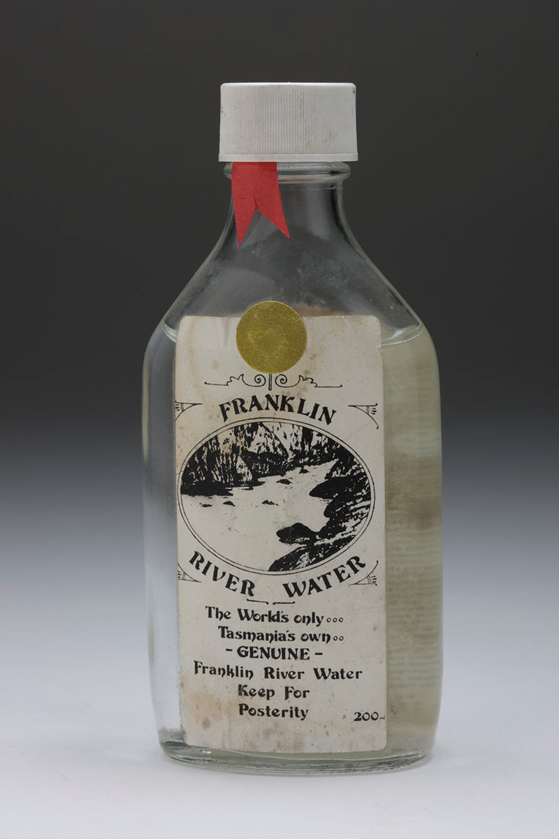 Studio shot of bottle of water with a dirty label reading Franklin River water. The world's only. Tasmania's own. Genuine Franklin River Water. Keep for posterity. 200 ml. - click to view larger image