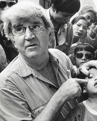 Fred Hollows points to the left eye of a young boy at a busy clinic in Vietnam. - click to view larger image