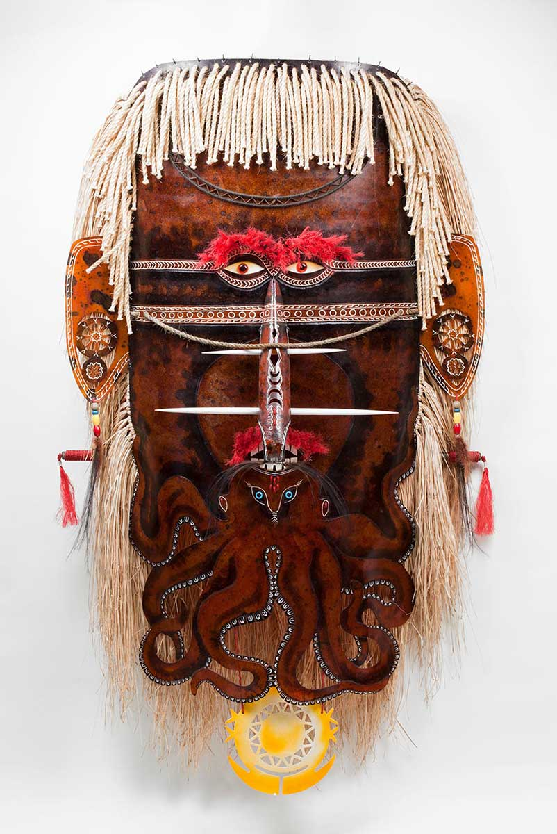 A brown coloured fibreglass mask with red plastic eyes. An octopus design is incorporated into the nose and mouth area with legs forming a beard. The ears are decorated with white linear designs and earrings made of beads and feathers. The nose is decorated with white linear designs, feathers and two nose ornaments. The hair is made from grass and rope.   - click to view larger image