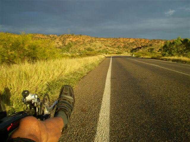 Colour photograph showing the front section of a recumbent bicycle and part of a man's leg, with this cycling shoe resting on a pedal. The bike is at the far left of a bitumen road, with a scrubby hill and cloudy sky ahead.