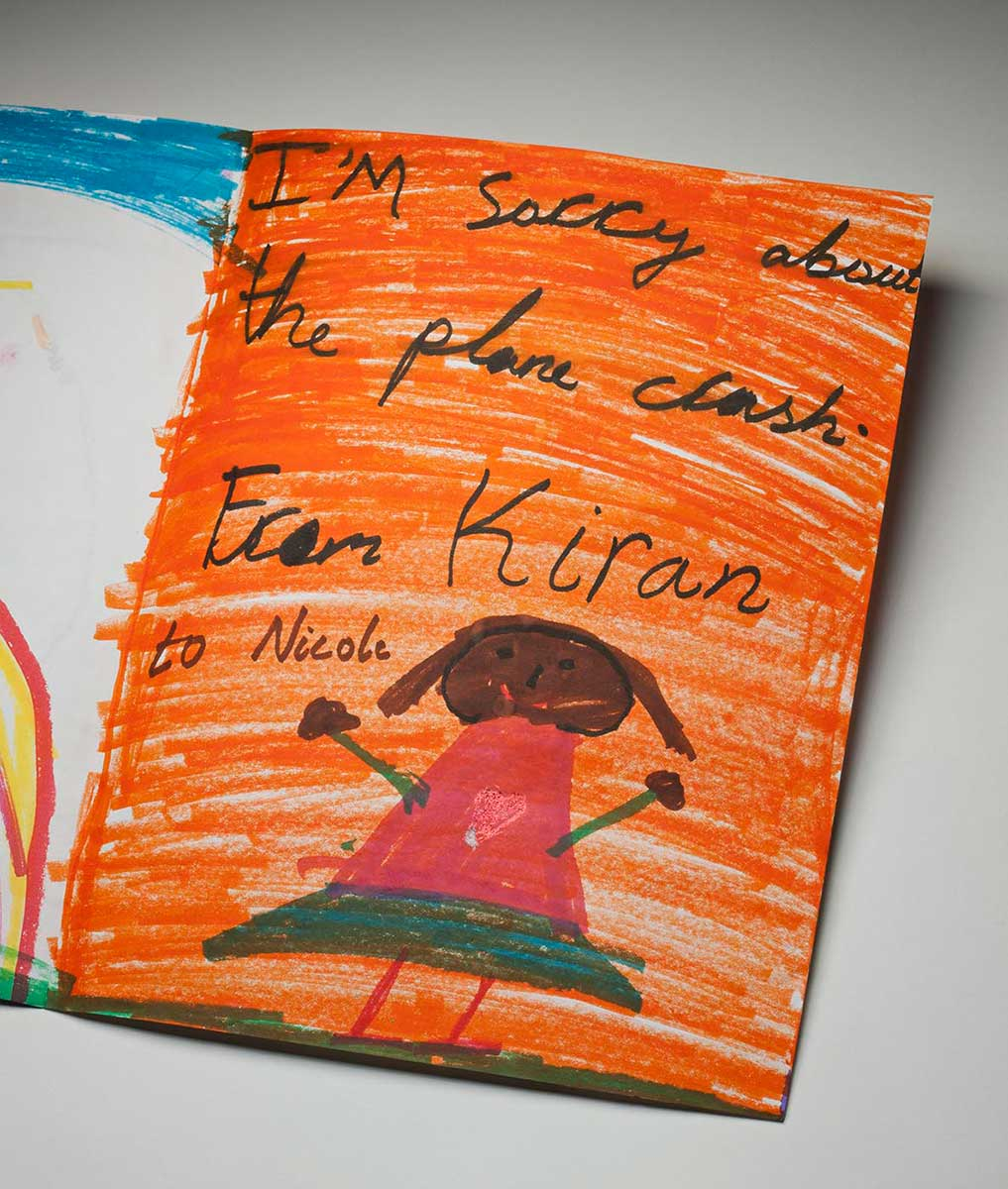 A handmade card showing the right inside view. The background is coloured in orange texta, with the handwritten words 'I'm sorry about the plane crash. From Kiran to Nicole' at top. There is a picture of a girl at the bottom of the card. She wears a pink top with a central heart motif, and a green skirt. She is smiling and her arms are stretched open. - click to view larger image