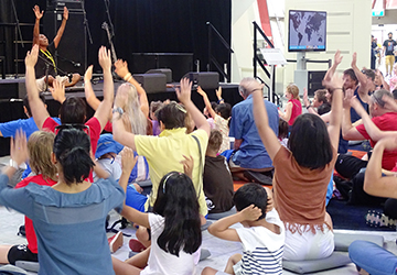 Woman sitting on a stage with audience of men, women and children sitting on the floor, raising their hands above their heads.
