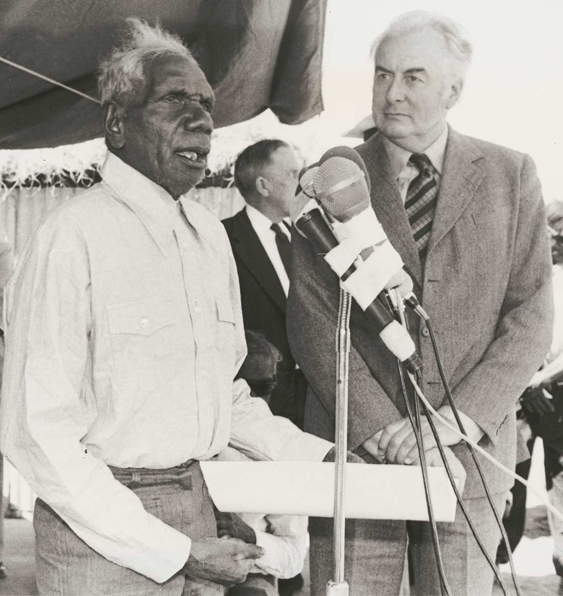 Two men standing at a microphone. - click to view larger image