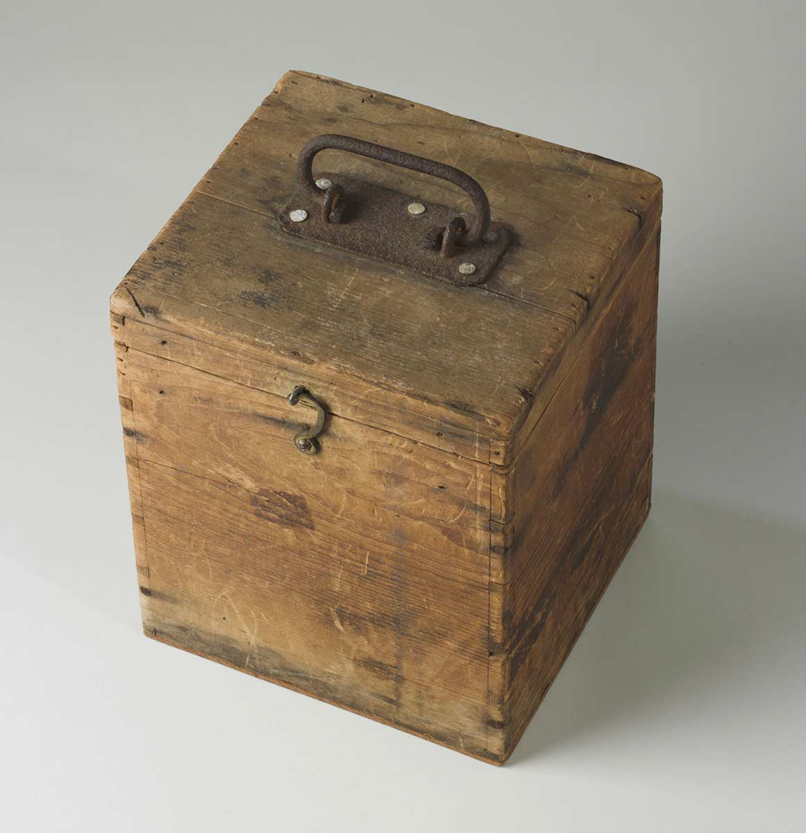 Wooden box with a lid. It has a small metal latch hook at the front and a rusted metal handle on top. - click to view larger image