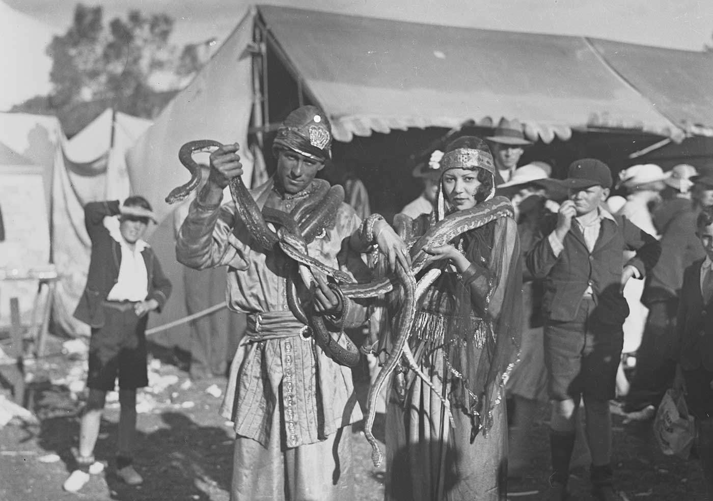 A man and a woman with snakes draped around their necks. Several onlookers are visible in the background. - click to view larger image