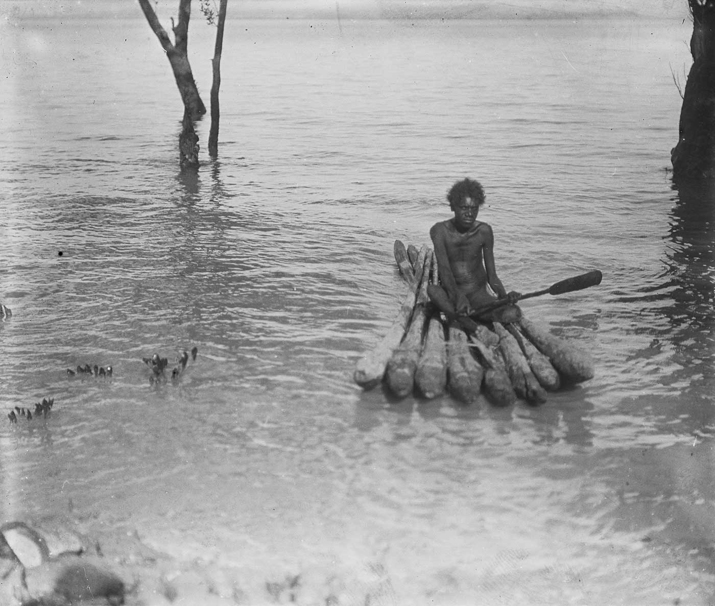 Black and white photograph of a man sitting on a raft on a body of water. - click to view larger image