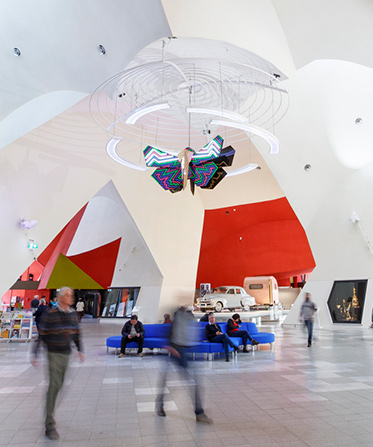 Image showing the interior of a building with people moving through the space and a colourful moth sculpture hanging from the ceiling.