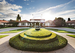 Landscape image showing a circular, tiered hedge garden feature in front of a low white building.