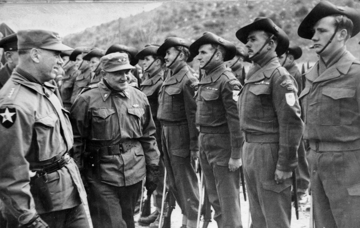 A short, smiling man in his fifties or sixties in Army uniform inspects Australian soldiers standing at attention.