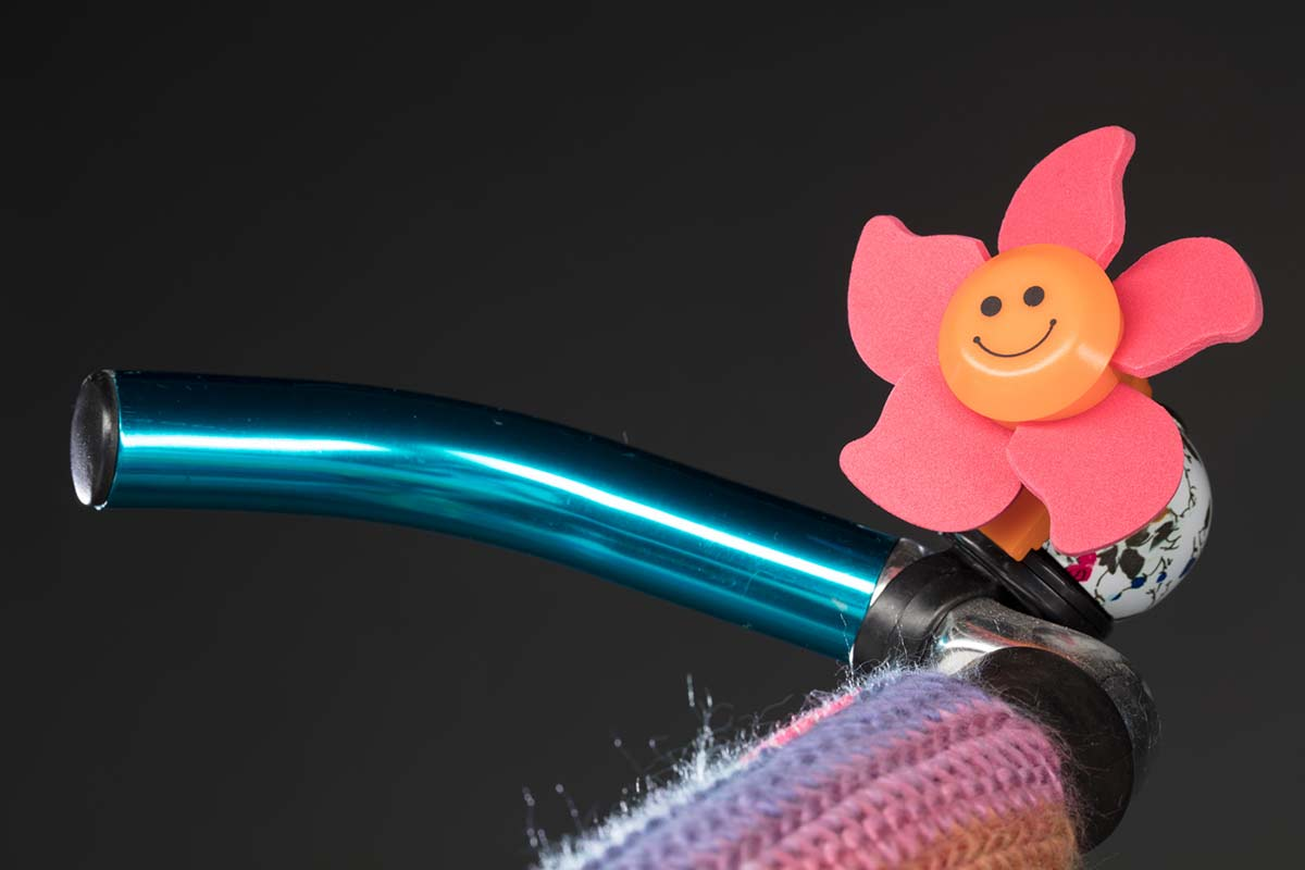 Blue bike handle and bell covered in a pink flower with a yellow smiley face at its centre. - click to view larger image