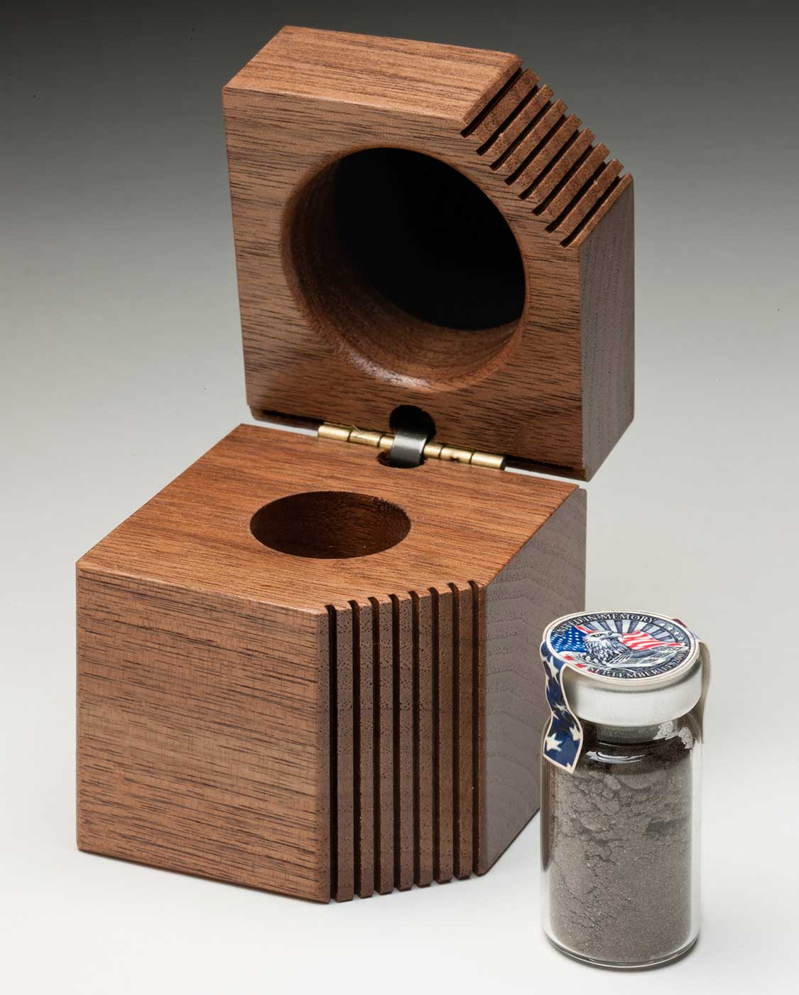 An opened timber box with a small glass vial filled with soil. - click to view larger image
