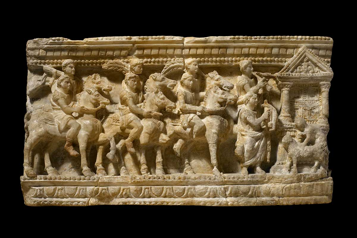 A marble carving showing a procession of people riding horses and playing musical instruments - click to view larger image