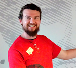 A bearded man wearing a bright red shirt stands in front of a large image which features an illustrated face.