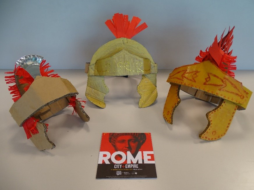 A photography of three handcrafted Roman helmets. A book with the title in large white letters, ROME, sits in the middle of the display.