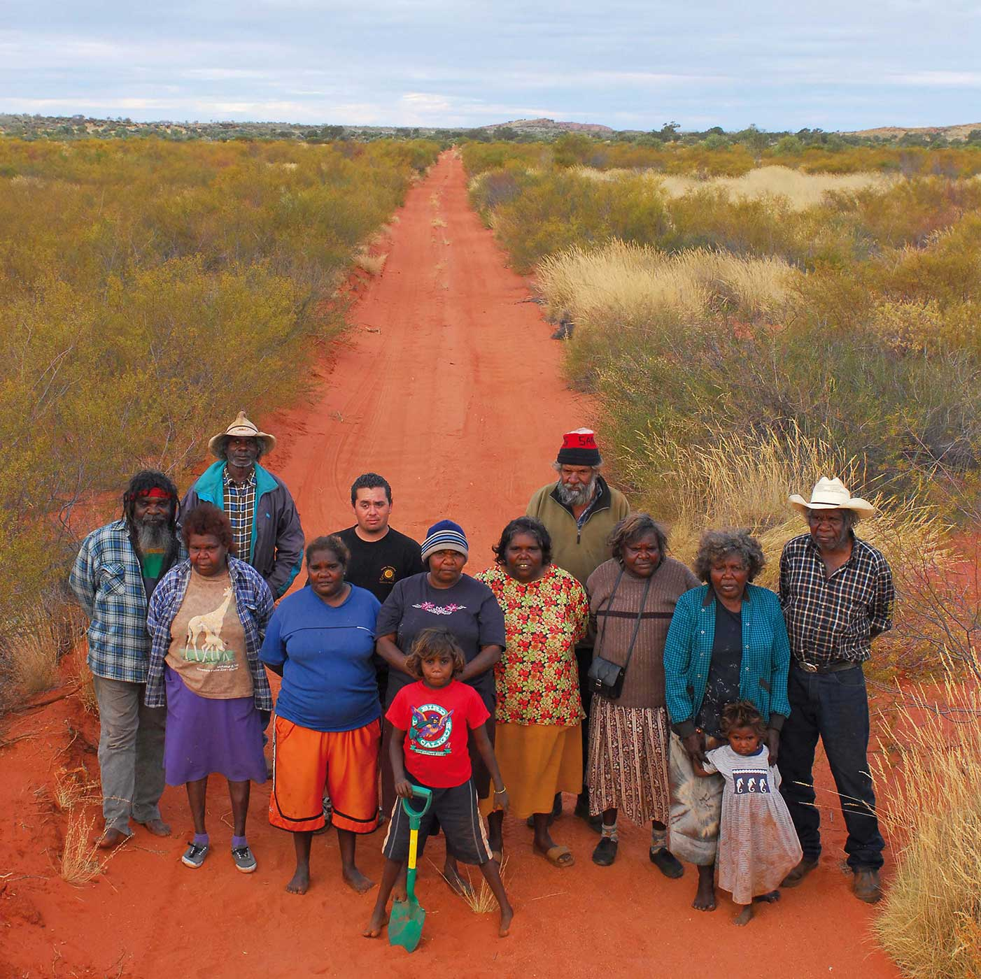 A group shot of people standing on a red dirt road. - click to view larger image