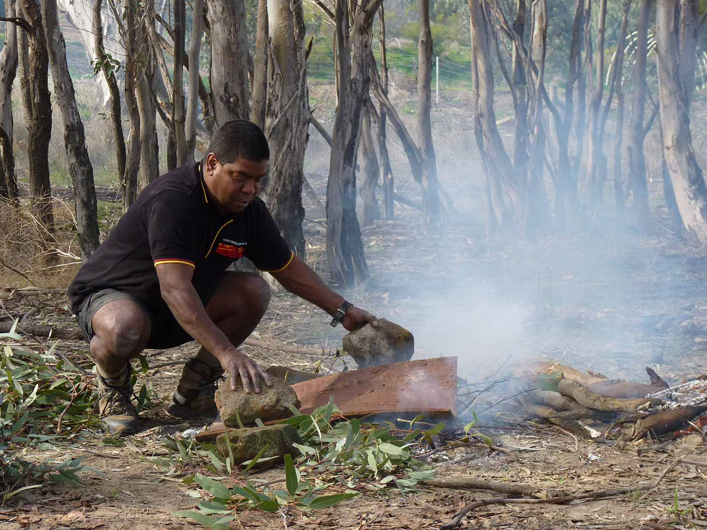 Jida Gulipilil making a bark etching by a fire. - click to view larger image