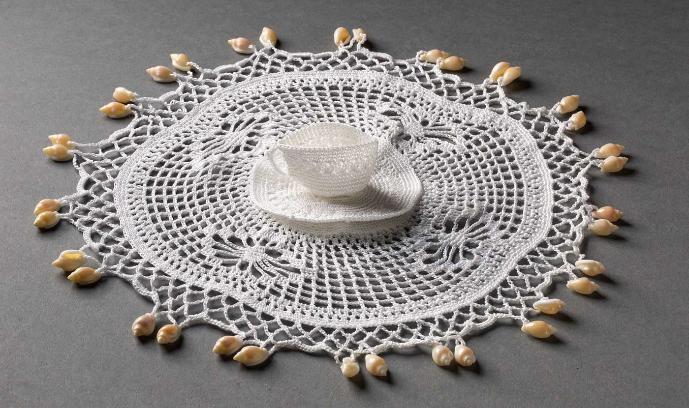 Circular white crocheted piece with three-dimensional tea cup on saucer at centre, and pairs of small beige shells decorating the circumference. - click to view larger image
