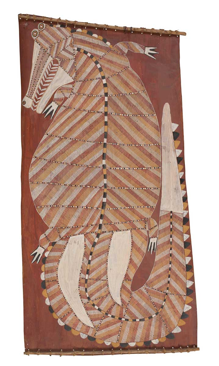 A bark painting worked with ochres on bark and on wooden restrainers. It depicts a crocodile with its head turning to the left and its tail curled up to the right. The crocodile has a yellow, white and brown crosshatched design with white feet, tail, and lower jaw. The painting has a red background. - click to view larger image
