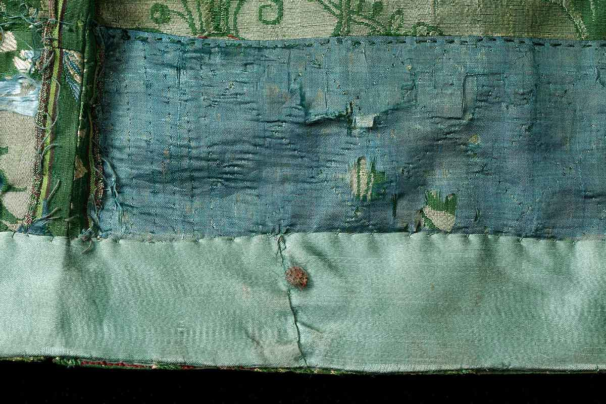 A detail image of the frayed hem of a green dress. - click to view larger image