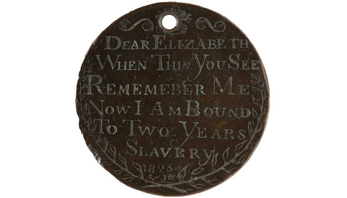 A convict love token, made up of a coin, engraved on this side features the text 'DEAR ELIZABETH / WHEN THIS YOU SEE / REMEMBER ME / NOW I AM BOUND / TO TWO YEARS / SLAVERY / 1825' with crossed sprigs at the bottom. The token has a hole pierced in it.