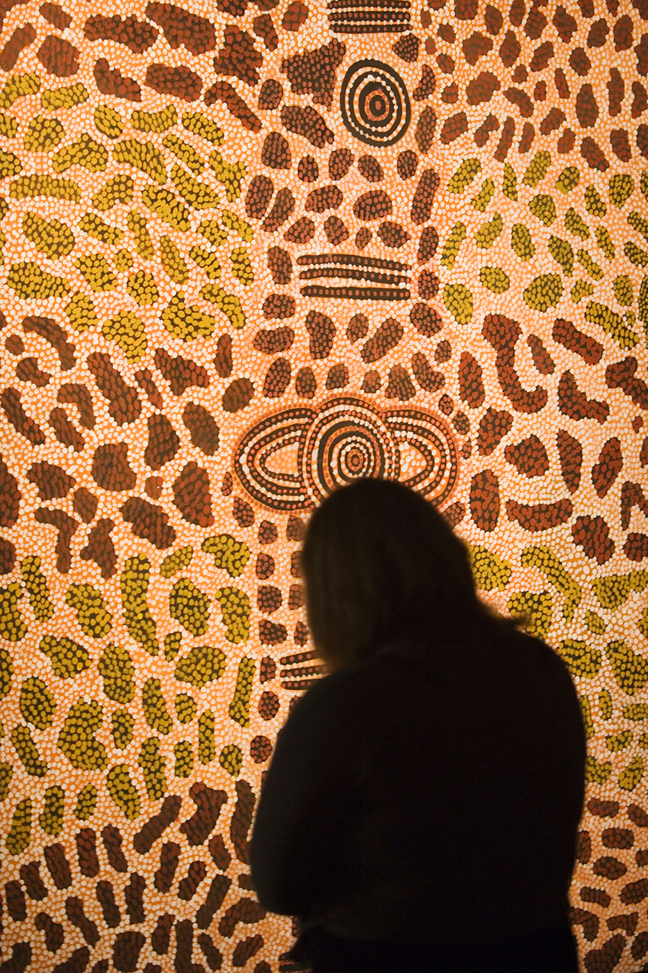 Rear silhouette of visitor looking at dot painting. - click to view larger image
