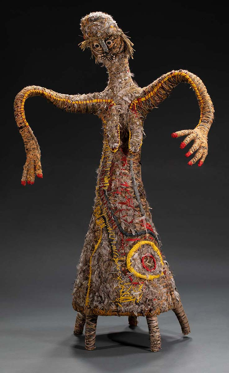 A tree sculpture baring human like features such as a face, hair, breasts, arms, fingers. The sculpture has five short legs instead of two and is made of various plant and synthetic materials. - click to view larger image