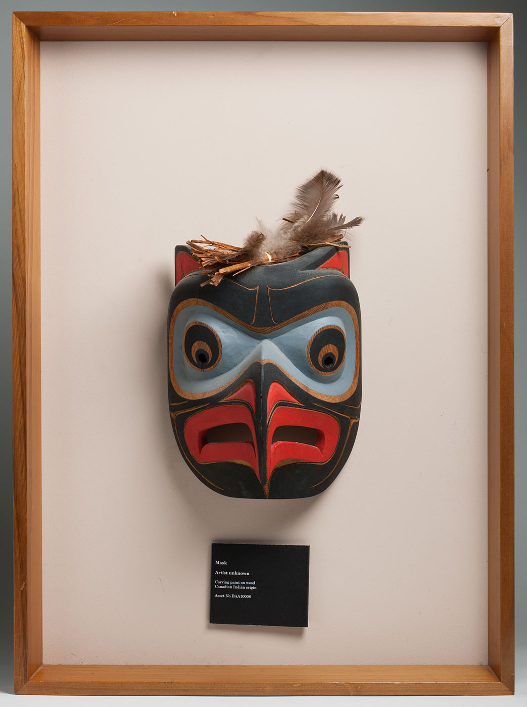 A carved and painted mask with feathers at the top. The mask sits in a light timber frame with white backing board. - click to view larger image