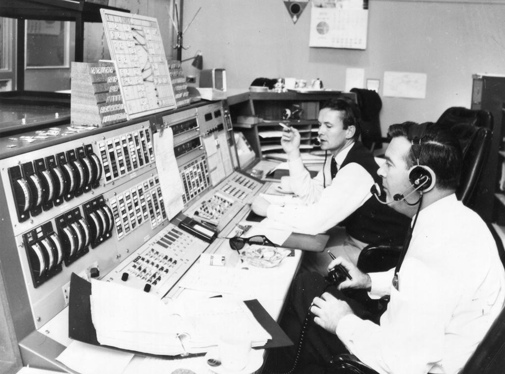 A black and white photo of two males operating an Apollo console. - click to view larger image