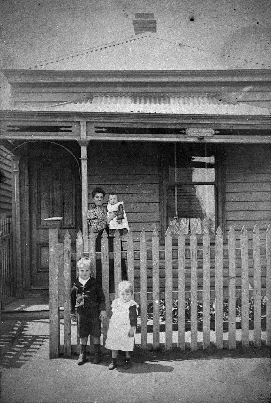 Black and white photo of a woman and three children outside a house. - click to view larger image