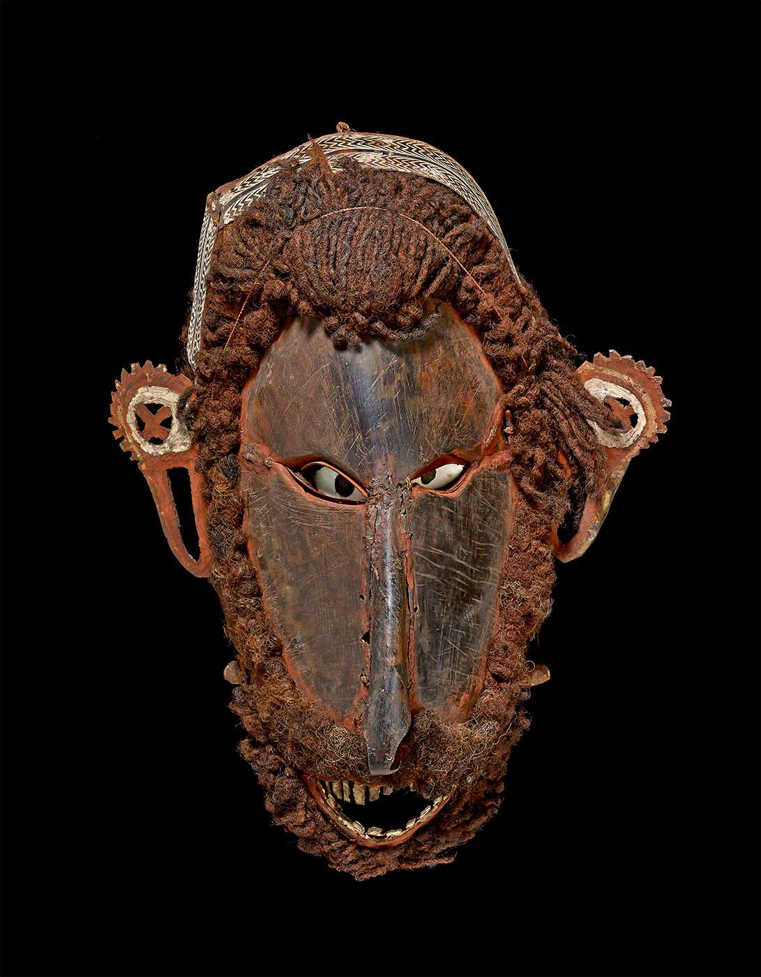 A mask made from turtle-shell plates which have been moulded and sewn into the form of an elaborate human face; hair and beard made from human hair; shell eyes. - click to view larger image