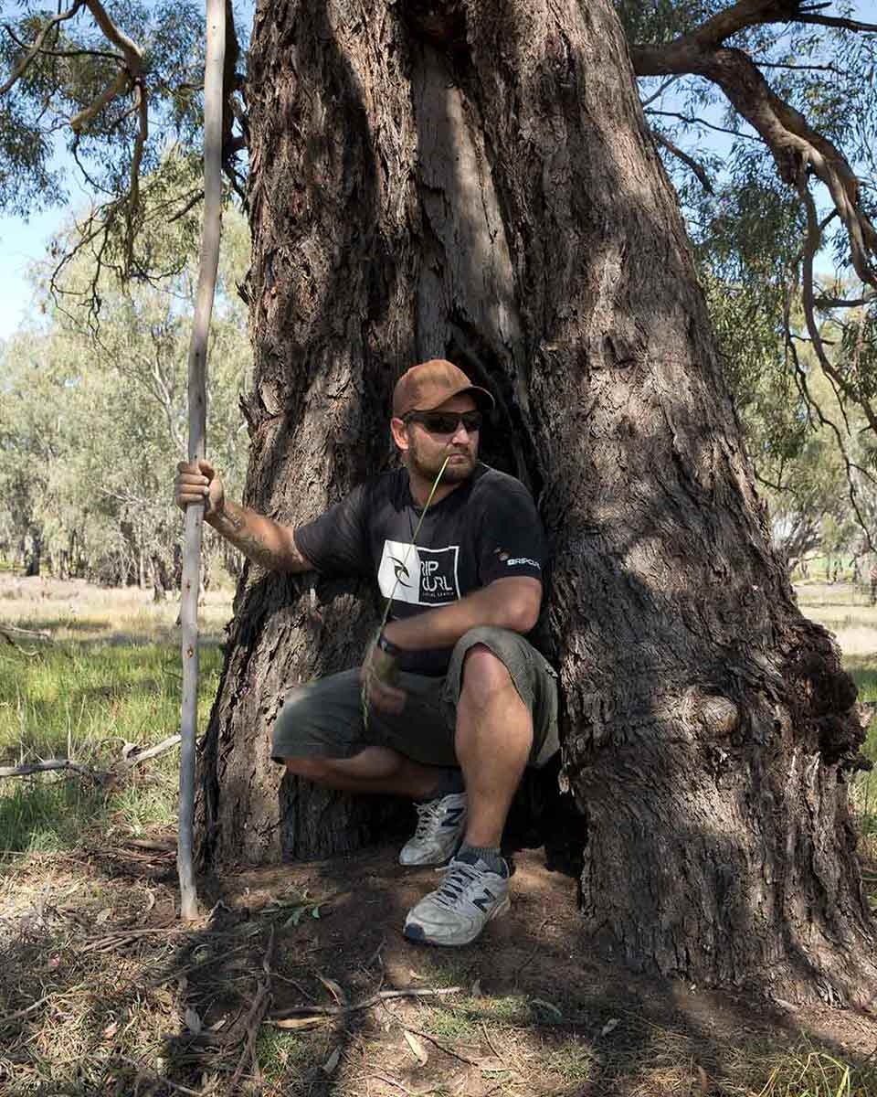 A man rests at the base of a large tree. - click to view larger image