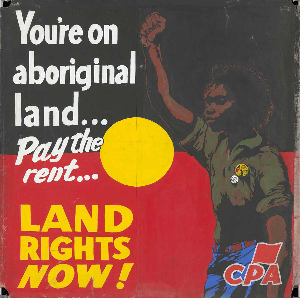 A protest banner hand painted on canvas, with the text 'You're on / aboriginal / land ... / Pay the rent ... / LAND RIGHTS NOW!'. An Aboriginal man stands to the right of the text with a raised fist. The background is the black, yellow and red of the Aboriginal flag, and a red 'CPA' logo is in the lower right corner. - click to view larger image
