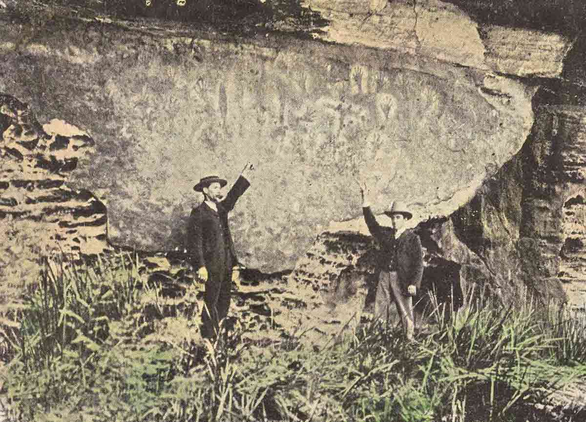 Postcard showing two men pointing up at hand stencils on a rock face. - click to view larger image