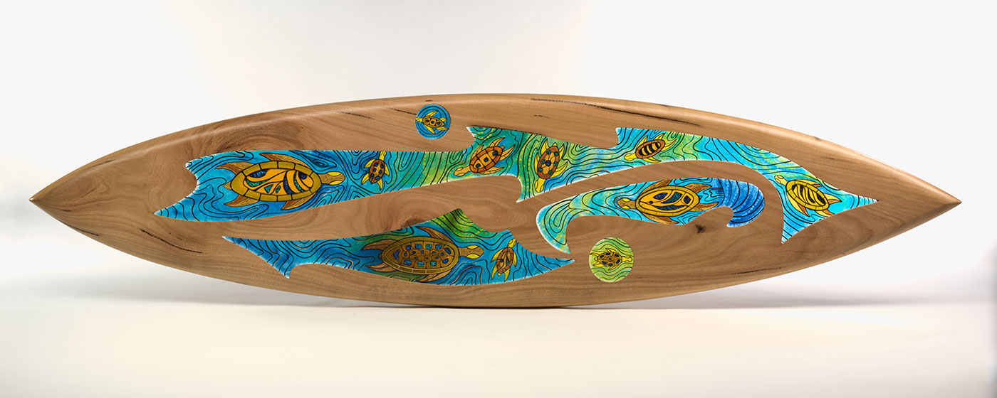 A sculpture made of carved wood in the shape of a surfboard inset with infused coloured glass, featuring turtle motifs swimming through water. - click to view larger image