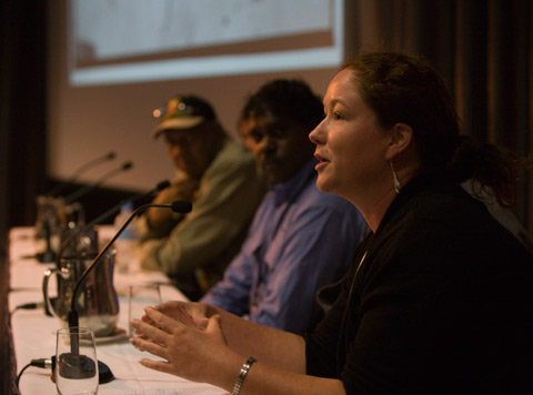 Three Indigenous speakers sitting at a table on the stage in the Museum's theatre. The camera looks down the length of the table through the microphones, glasses and water jugs. The lower part of a large projection screen is visible out of focus in the background.