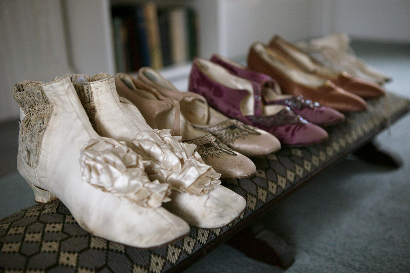 Colour photograph of five pairs of ladies shoes lined up on a low stool.