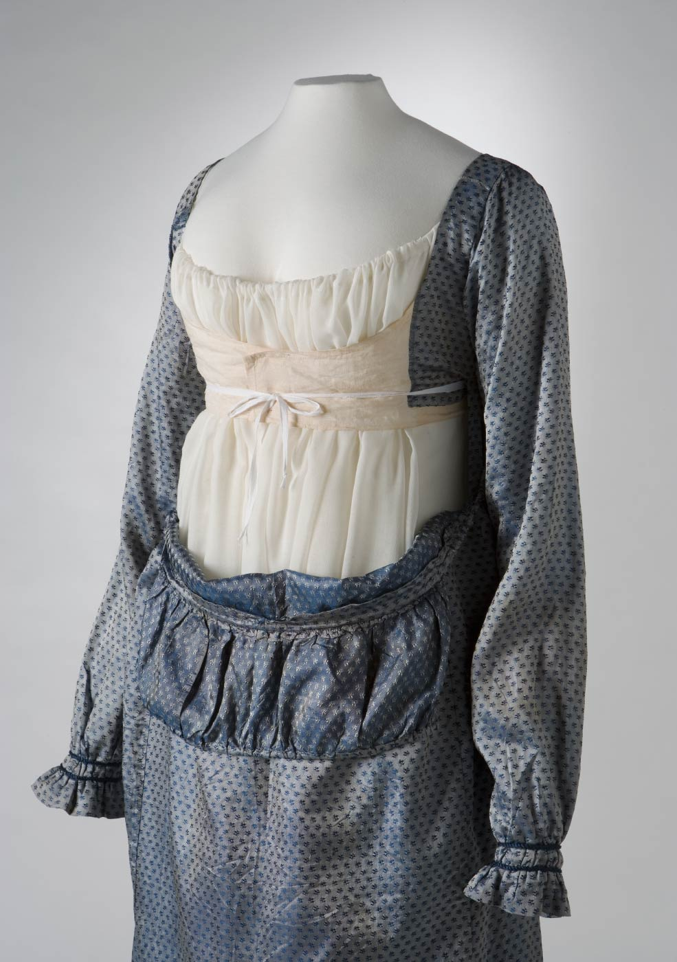 Front view of a blue silk full length empire-line dress with the bib-front down and the bodice revealed. - click to view larger image