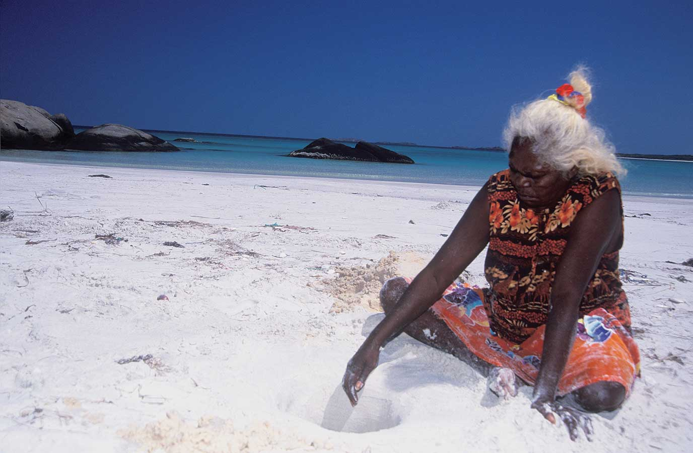 A colour photograph of Dhuwarrwarr Marika sitting on a beach, digging a hole in the white sand. She wears a brightly coloured dress and has her long grey hair tied back behind her head. She sits at the right of the photograph. The sandy beach is to the left and behind her. In the middle and left background are some large smooth boulders in the water. A distant shore appears on the horizon. The cloudless blue sky is in the top third of the photograph. - click to view larger image