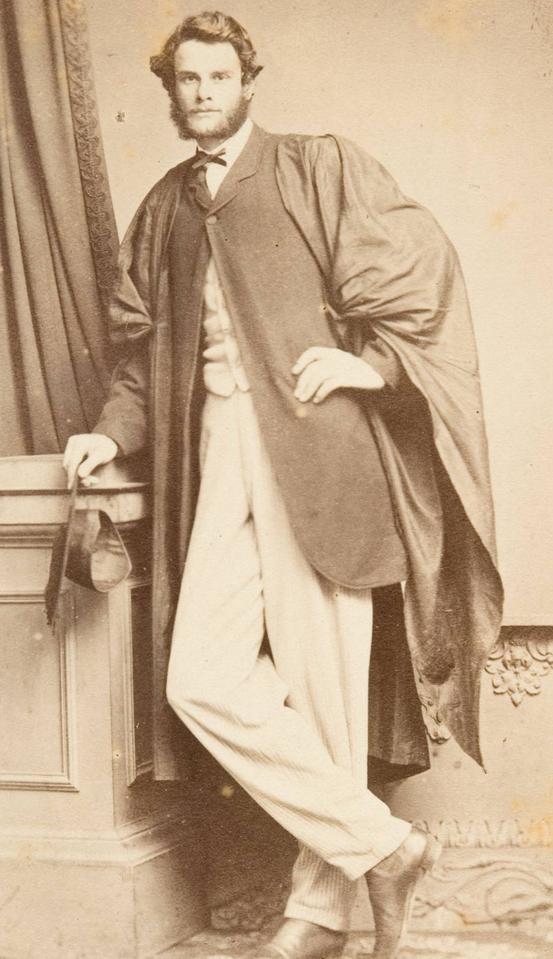 Man posing for photograph in academic gown leaning with right arm resting on a cabinet, with right leg crossed in front of leg and right shoe tip touching the ground and with left hand on waist - click to view larger image