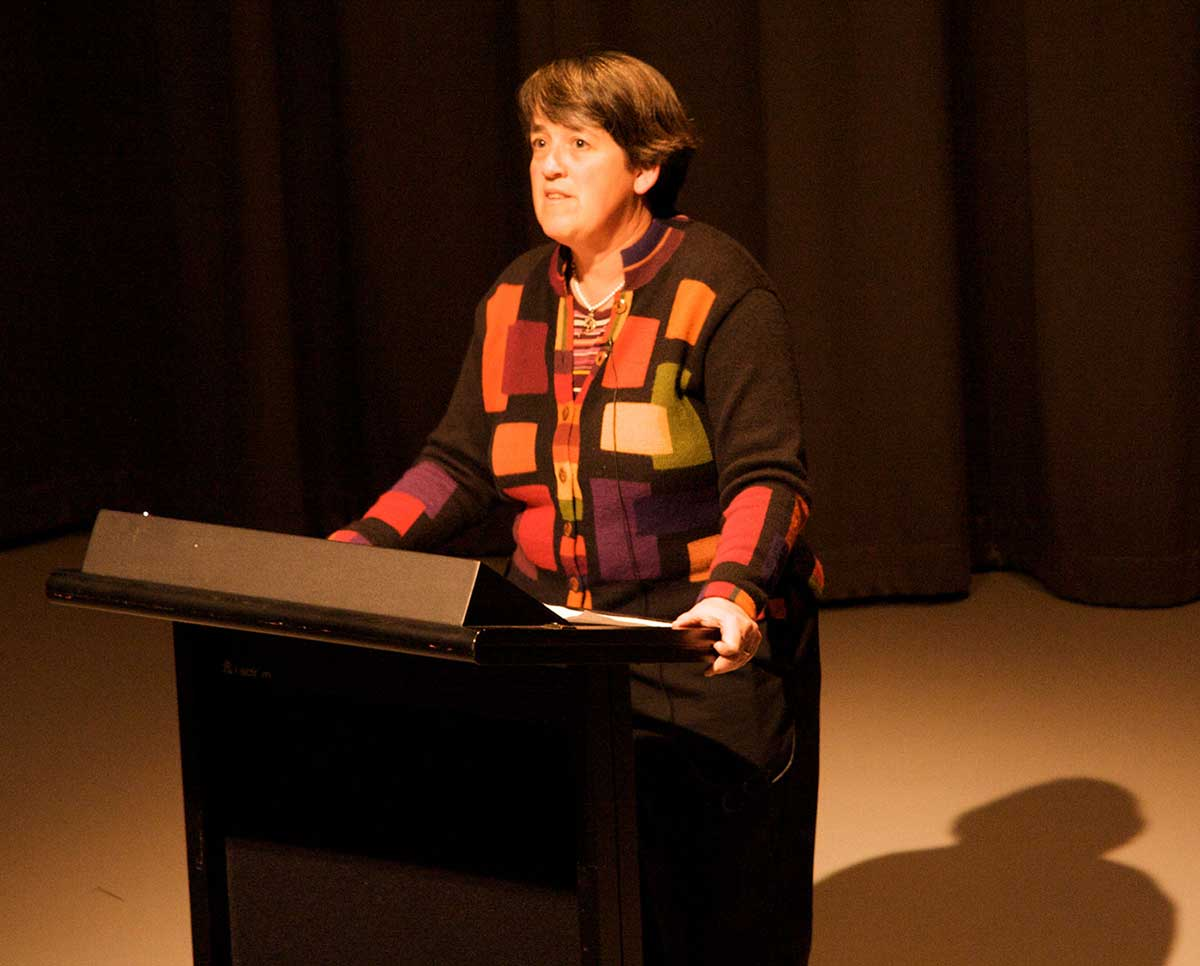 A woman stands at a lectern on a stage. - click to view larger image
