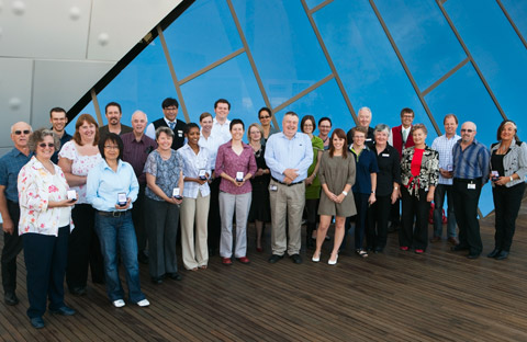 A group of 27 male and female Museum staff standing in two rows, those in front holding small presentation cases. The group stands on a timber deck. Behind them is part of a large window with diagonal reinforcing strips and reflecting very blue sky. Part of the museum's wall is visible in the upper left corner of the image. It is silver and has four bumps in it.