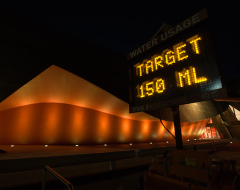 An electronic sign outside a museum, at night. The sign is at the right of the photograph. It has a display which is headed 'Water Usage', in white letters. Under the heading, in a light readout, is 'Target 150 ML'. The letters in the readout are yellow. Behind the sign is part of the museum's exterior. It is a curved wall that is lit up by a row of lights in the ground. The wall is orange in colour. To the far left of the photograph can just be made out what appears to be the entrance to the museum.