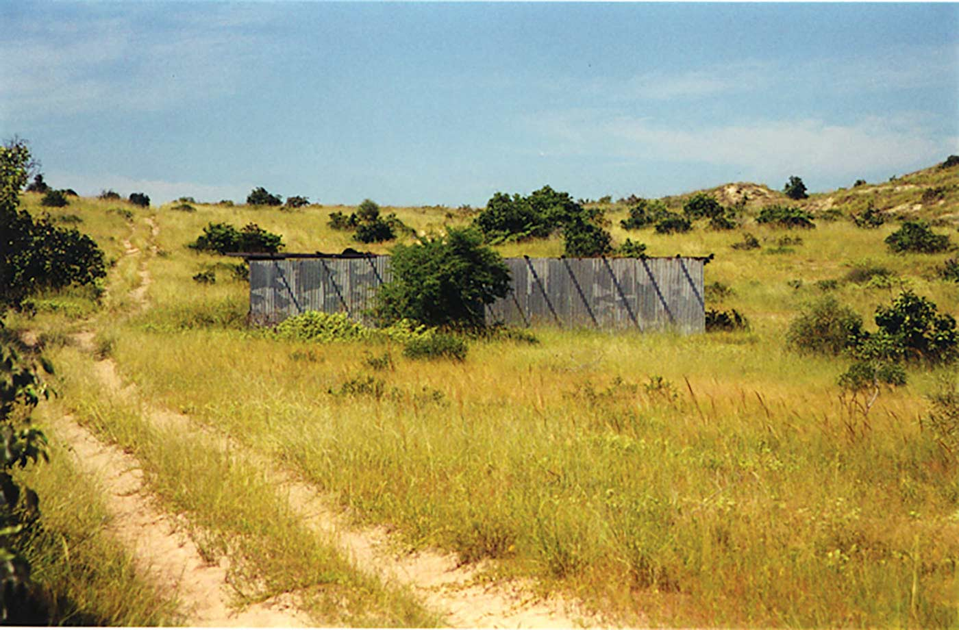 A colour photograph of an abandoned building surrounded by grass-covered sand dunes. The building is in the middle of the photograph. It has a flat roof and is partially obscured by some trees. In the left foreground is a vehicle track marked by parallel sandy lines. Scattered trees are on the dunes. The sky in the distance is light blue and has some very pale and wispy clouds in it. - click to view larger image