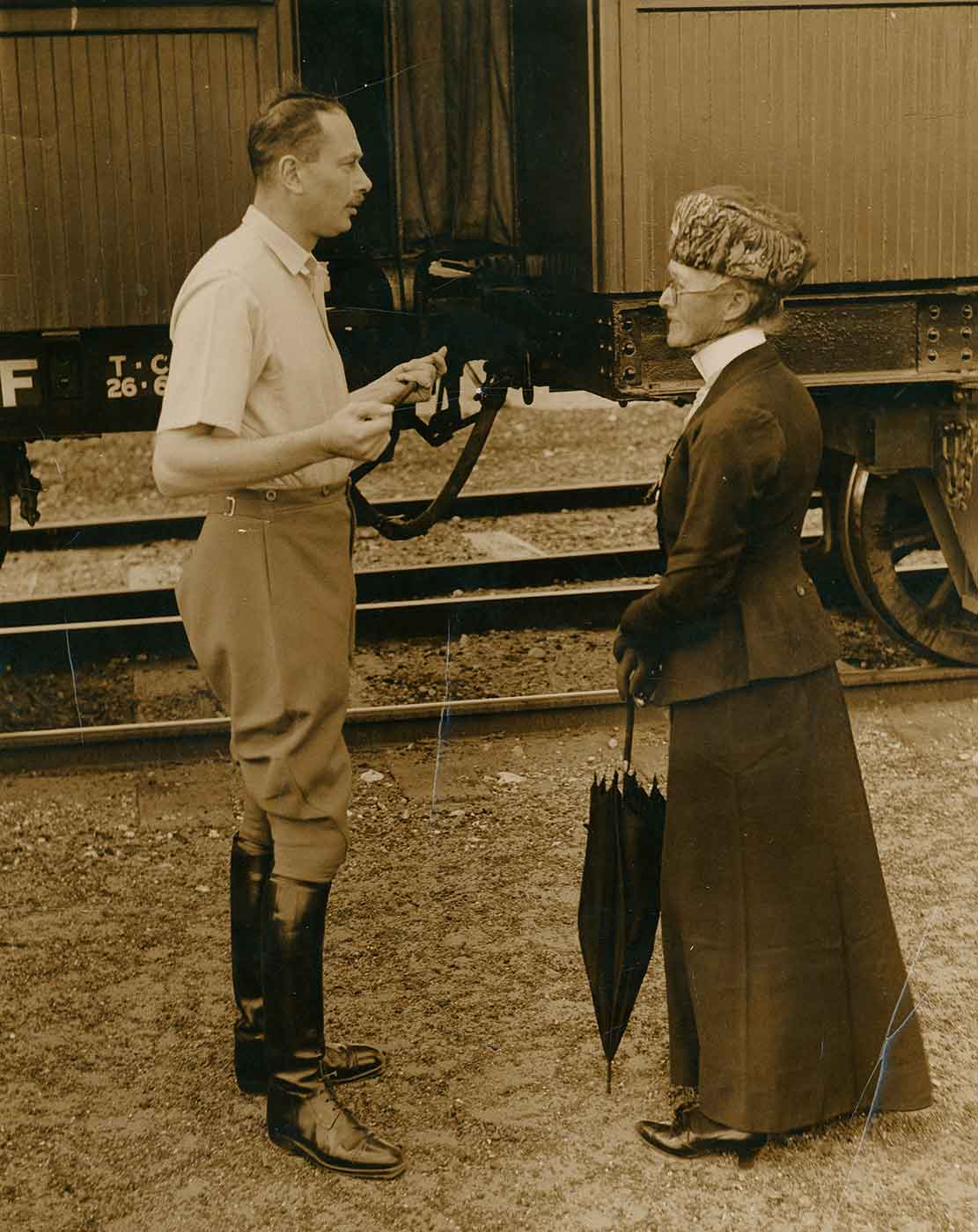 Black and white photo of a man in conversation with an elderly woman, standing next to a stationary train. - click to view larger image