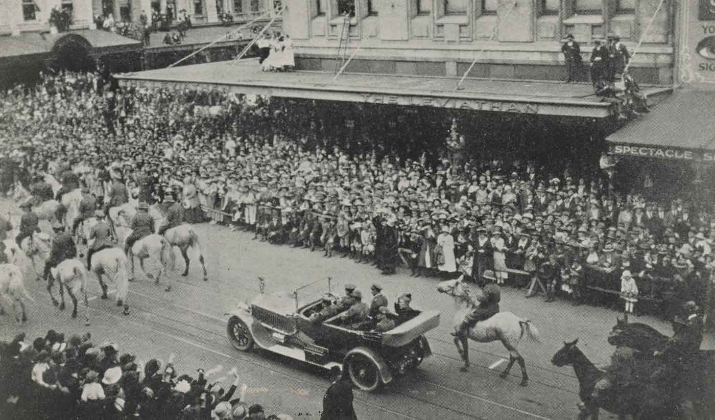 Black and white photo of a procession down a city street featuring horse and riders leading an automobile which is carrying several people, while crowds look on. - click to view larger image
