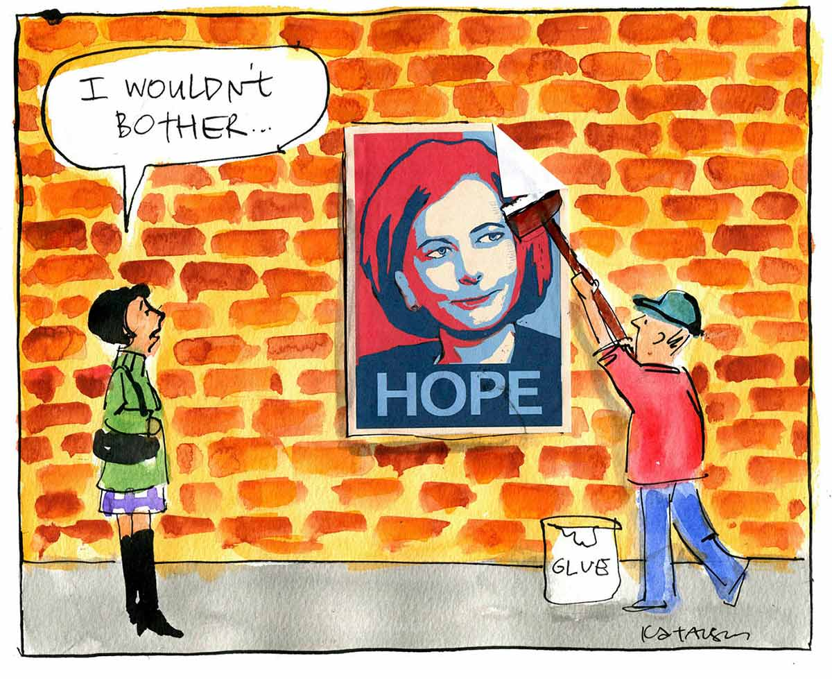 A colour cartoon depicting a man putting a poster up on a brick wall. The poster shows Julia Gillard, in red and blue. The word 'HOPE' is at the bottom of the poster. A woman stands to the left, watching the man. She is saying 'I wouldn't bother ...'  - click to view larger image